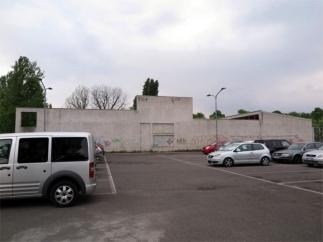 Il parcheggio in fondo a via Cazzaniga e la facciata della Casa dell'acqua rigorosamente senza porte e finestre, come si presenta oggi.