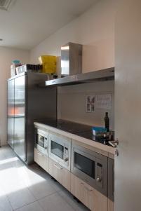 I forni e i piani di cottura a induzione della cucina dello stabile su via Rombon per i residenti che non hanno cucina in camera. Oltre a dispensa frigorifera