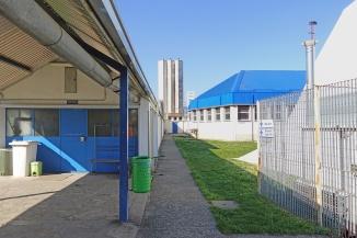 A sinistra i locali in cui verrà realizzata una piccola palestra per ginnastica dolce. In fondo i camini della centrale termica e a destra una delle due palestre