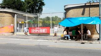 005 Si richiude il cancello per ora sono usciti 3 operai della INNSE che si apprestano a mangiare con i loro compagni